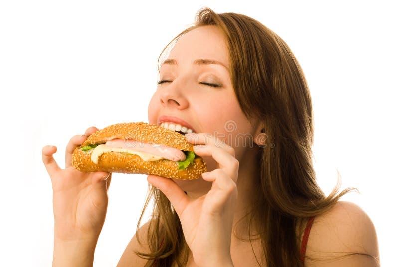 Mujer joven que come un perrito caliente imagen de archivo libre de regalías