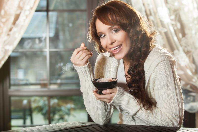 Mujer joven que come un postre imagenes de archivo
