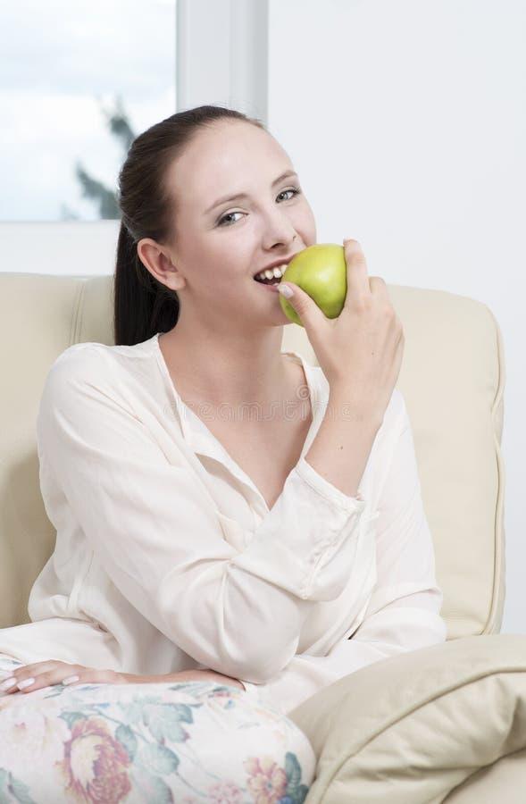 Mujer joven que come una manzana foto de archivo