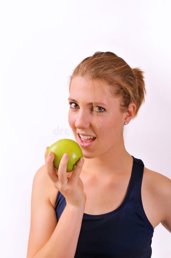 Mujer joven que come una manzana imagen de archivo libre de regalías