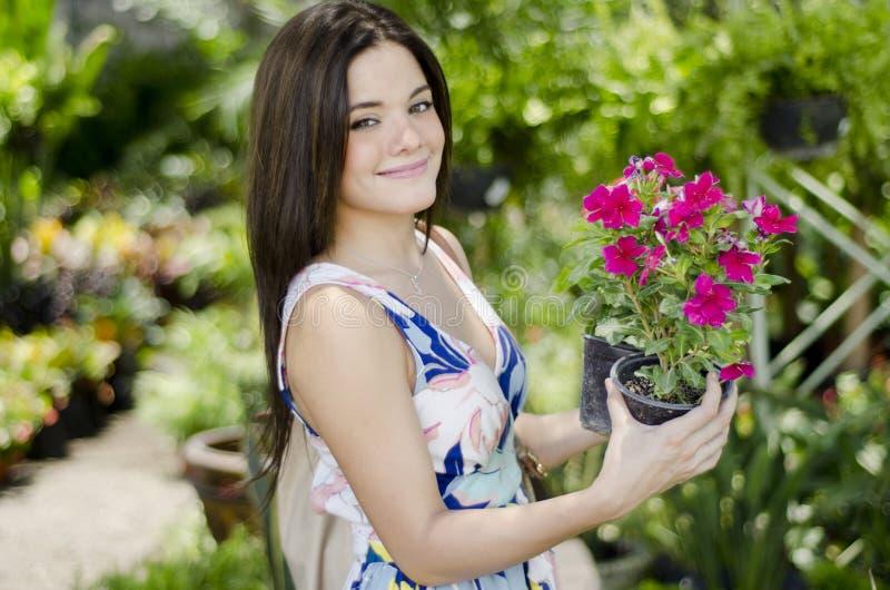 Mujer joven que compra algunas plantas imagen de archivo libre de regalías