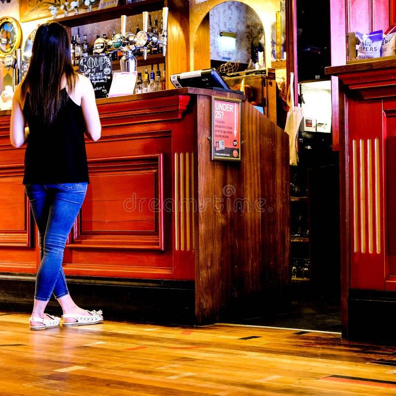 Mujer joven que compra una bebida fotos de archivo