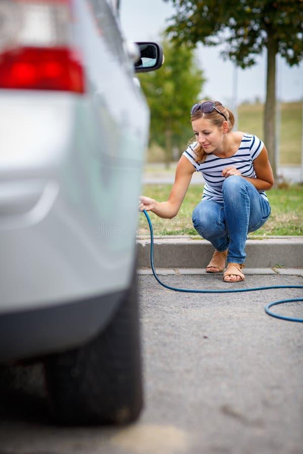 Mujer joven que comprueba la presión de neumático del coche fotografía de archivo libre de regalías