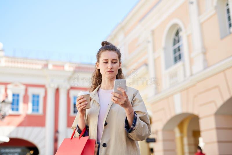 Mujer joven que comprueba SMS fotografía de archivo libre de regalías