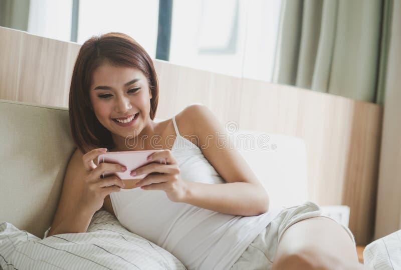 Mujer joven que comprueba su teléfono elegante que miente en cama foto de archivo
