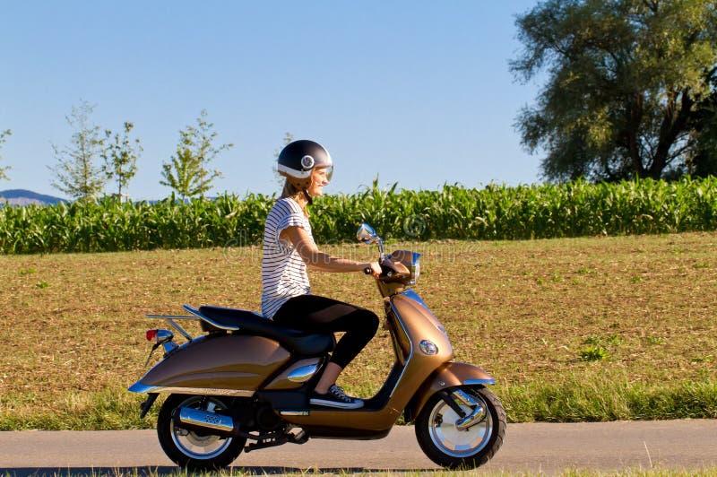 Mujer joven que conduce con la vespa de motor imagen de archivo