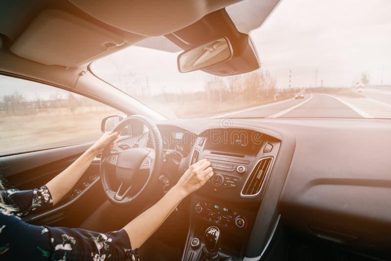 Mujer joven que conduce un coche y que ajusta el audio para el automóvil fotografía de archivo