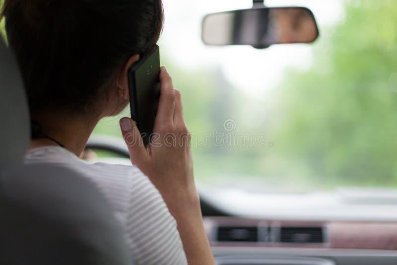 Mujer joven que conduce y que usa el teléfono celular fotos de archivo