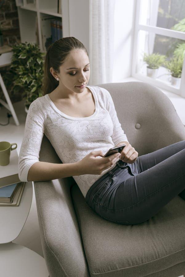 Mujer joven que conecta con su smartphone en casa fotografía de archivo libre de regalías