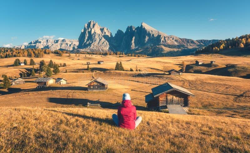 Mujer joven que considera en prados y montañas la puesta del sol en otoño imagen de archivo