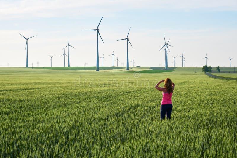 Mujer joven que considera hacia las turbinas de viento la salida del sol, en un campo del trigo verde Concepto para las solucione imagenes de archivo