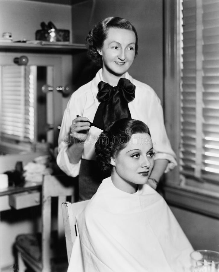 Mujer joven que consigue le el pelo hecho en un salón de pelo (todas las personas representadas no son vivas más largo y ningún e foto de archivo