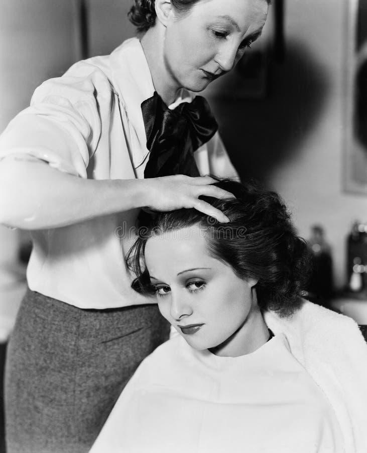 Mujer joven que consigue le el pelo hecho en un salón de pelo (todas las personas representadas no son vivas más largo y ningún e fotografía de archivo