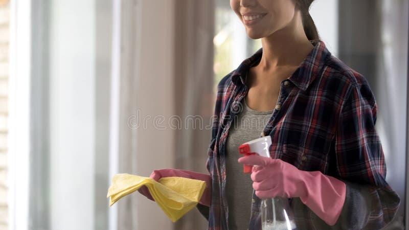 Mujer joven que consigue lista para la limpieza general, el espray de la tenencia y la manta amarilla fotos de archivo