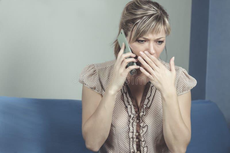 Mujer joven que consigue malas noticias por el teléfono imagen de archivo libre de regalías