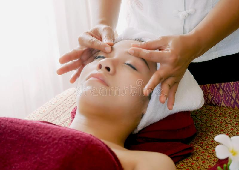 Mujer joven que consigue masaje de cara del balneario en el salón de belleza imagenes de archivo