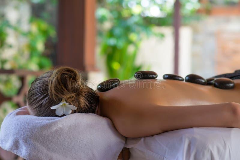 Mujer joven que consigue masaje de piedra caliente en salón del balneario Invitación de la belleza fotografía de archivo libre de regalías