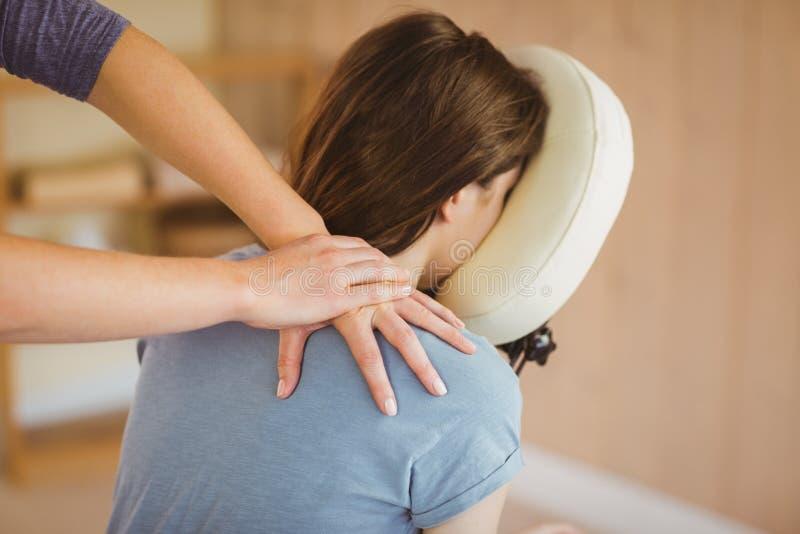 Mujer joven que consigue masaje en silla imagenes de archivo