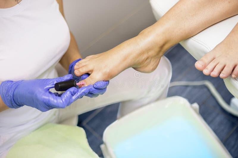 Mujer joven que consigue pedicura profesional en sal?n de belleza imágenes de archivo libres de regalías