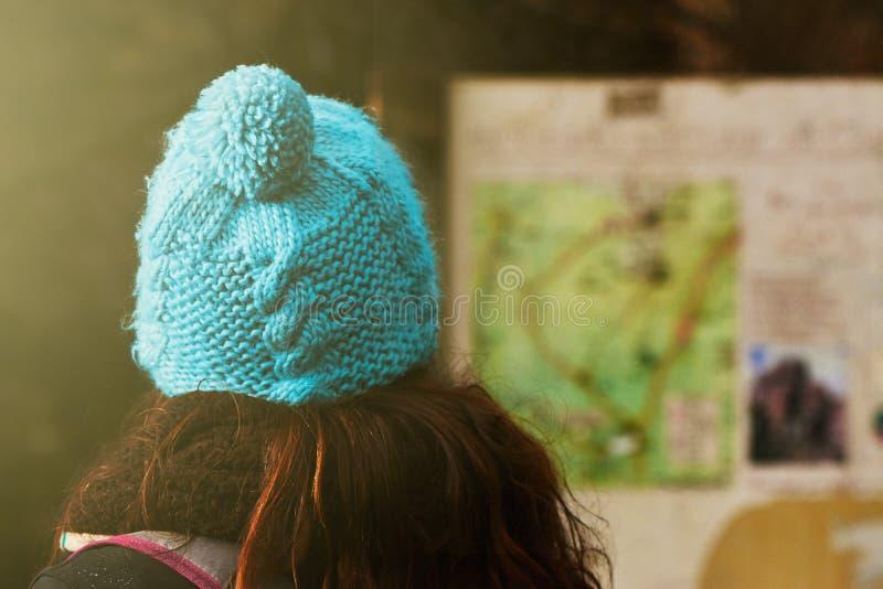 Mujer joven que consulta un tablero de la información del mapa, pistas de senderismo adentro fotografía de archivo
