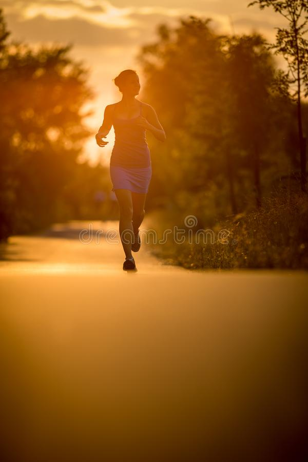 Mujer joven que corre al aire libre en evenis soleados preciosos de un verano foto de archivo libre de regalías