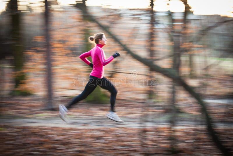 Mujer joven que corre al aire libre en un parque de la ciudad fotos de archivo