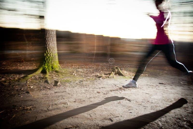 Mujer joven que corre al aire libre en un parque de la ciudad fotografía de archivo