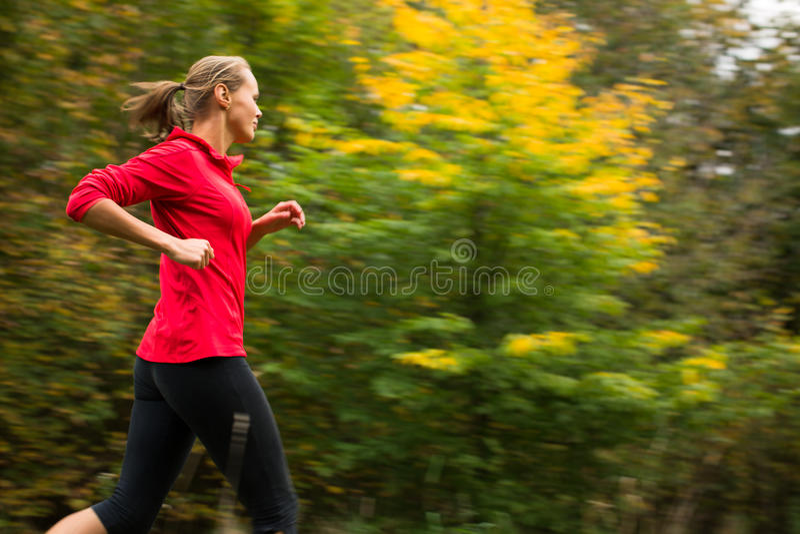 Mujer joven que corre al aire libre en un parque de la ciudad imagen de archivo