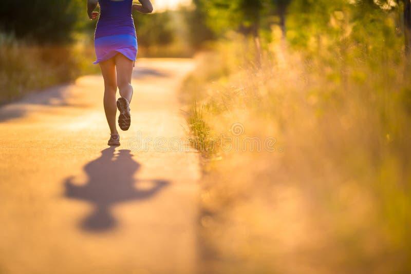 Mujer joven que corre al aire libre en una tarde soleada preciosa del verano fotografía de archivo libre de regalías