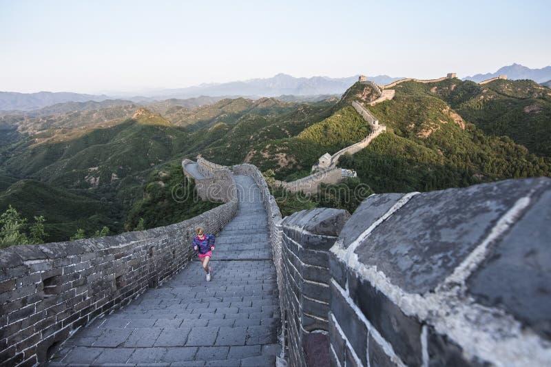 Mujer joven que corre en la Gran Muralla china fotografía de archivo