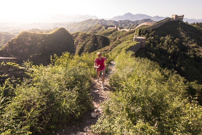 Mujer joven que corre en la Gran Muralla china imagen de archivo