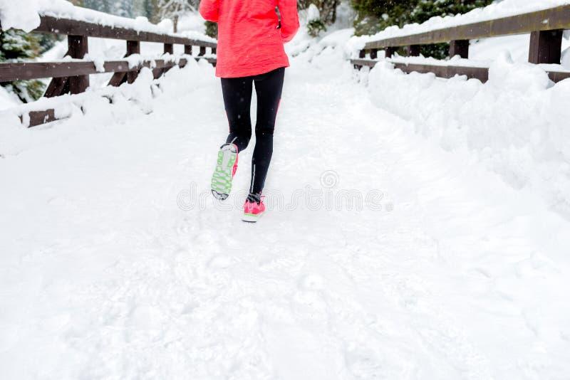 Mujer joven que corre en nieve en las montañas del invierno que llevan guantes calientes de la ropa en tiempo de la nieve foto de archivo libre de regalías
