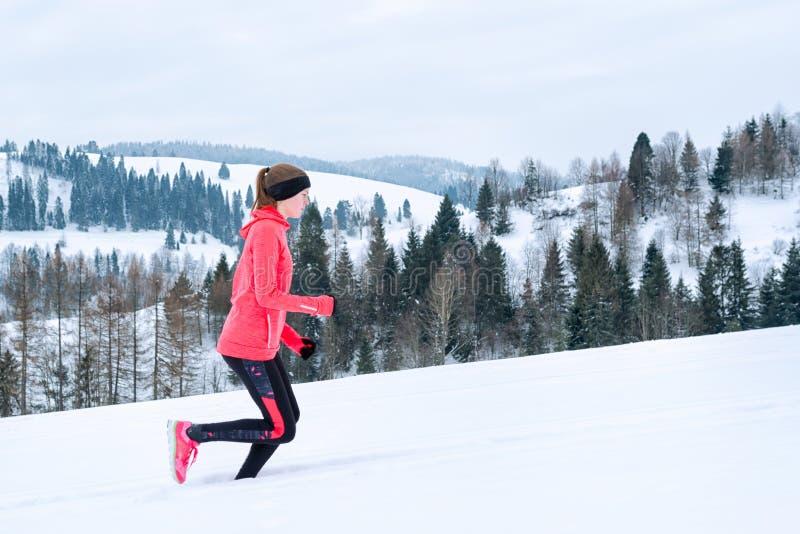 Mujer joven que corre en nieve en las montañas del invierno que llevan guantes calientes de la ropa en tiempo nevoso imagenes de archivo