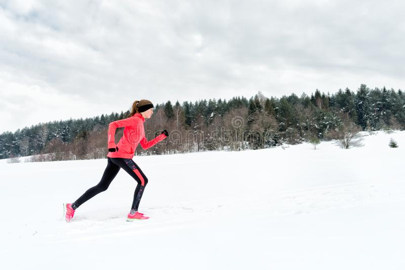 Mujer joven que corre en nieve en las montañas del invierno que llevan guantes calientes de la ropa en tiempo nevoso fotos de archivo