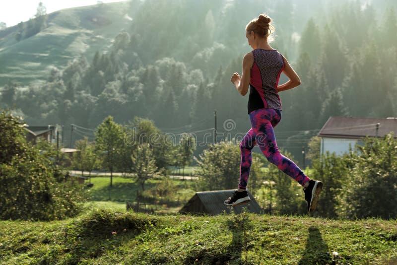 Mujer joven que corre en rastro de montaña fotografía de archivo libre de regalías