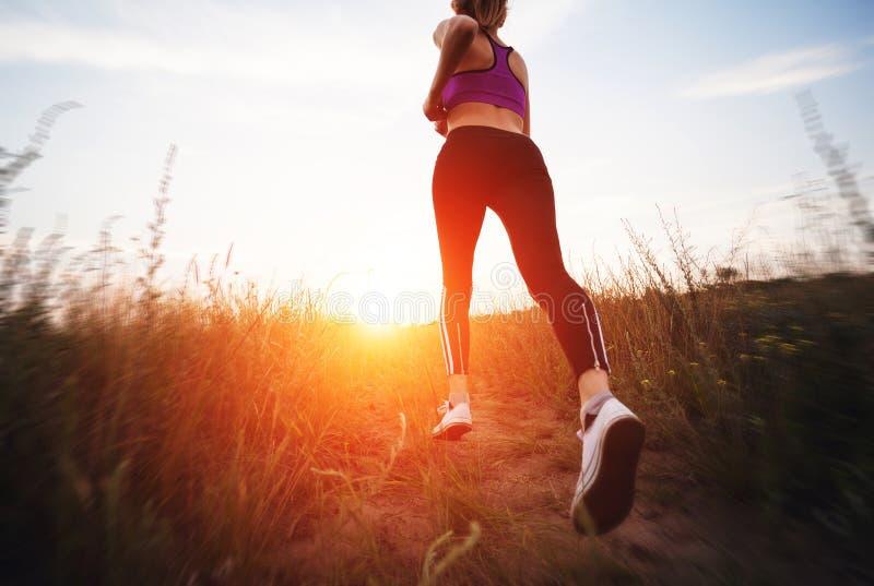 Mujer joven que corre en un camino rural en la puesta del sol fotos de archivo