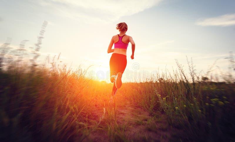 Mujer joven que corre en un camino rural en la puesta del sol imagenes de archivo