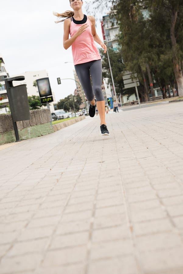 Mujer joven que corre más allá de un trashcan fotografía de archivo libre de regalías