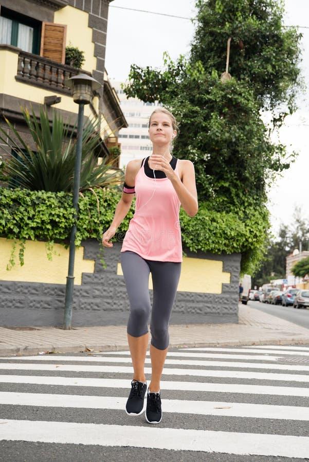 Mujer joven que corre a través de un paso de cebra imagenes de archivo