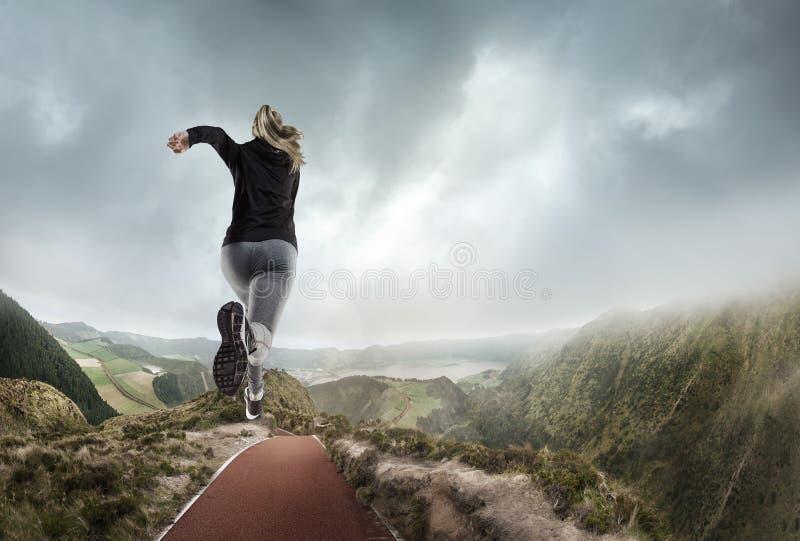 Mujer joven que corre y que salta cerca de las montañas y del lago imagen de archivo