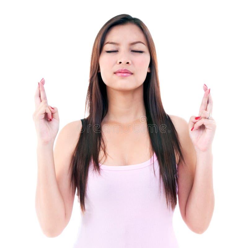 Mujer joven que cruza sus dedos fotografía de archivo