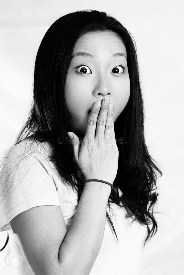 Mujer joven que cubre su boca fotografía de archivo libre de regalías