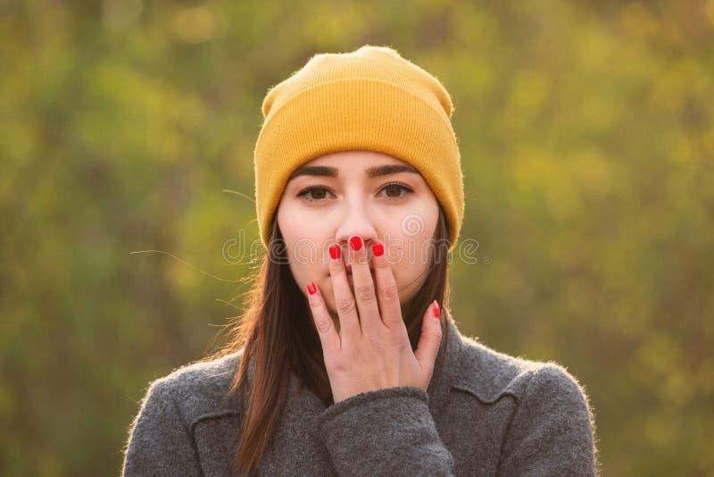 Mujer joven que cubre su boca con su mano fotografía de archivo libre de regalías