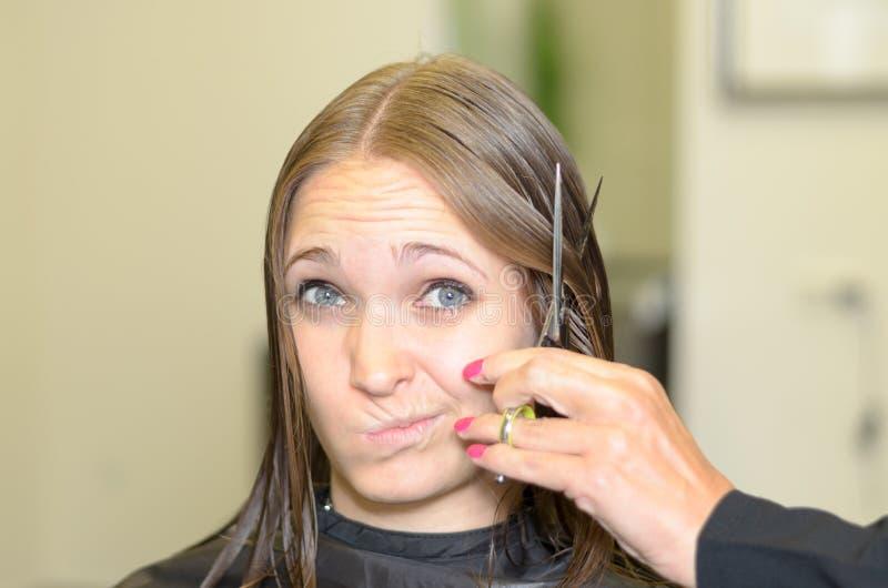 Mujer joven que da al peluquero una mirada dudosa fotos de archivo libres de regalías