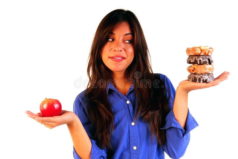 Mujer joven que decide entre la manzana o los anillos de espuma foto de archivo libre de regalías