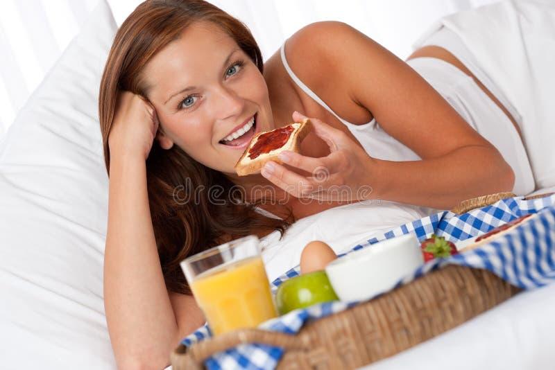 Mujer joven que desayuna hecha casero