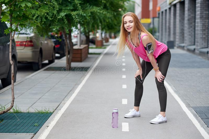 Mujer joven que descansa después de correr en un carril de la ciudad con una botella de agua fotos de archivo