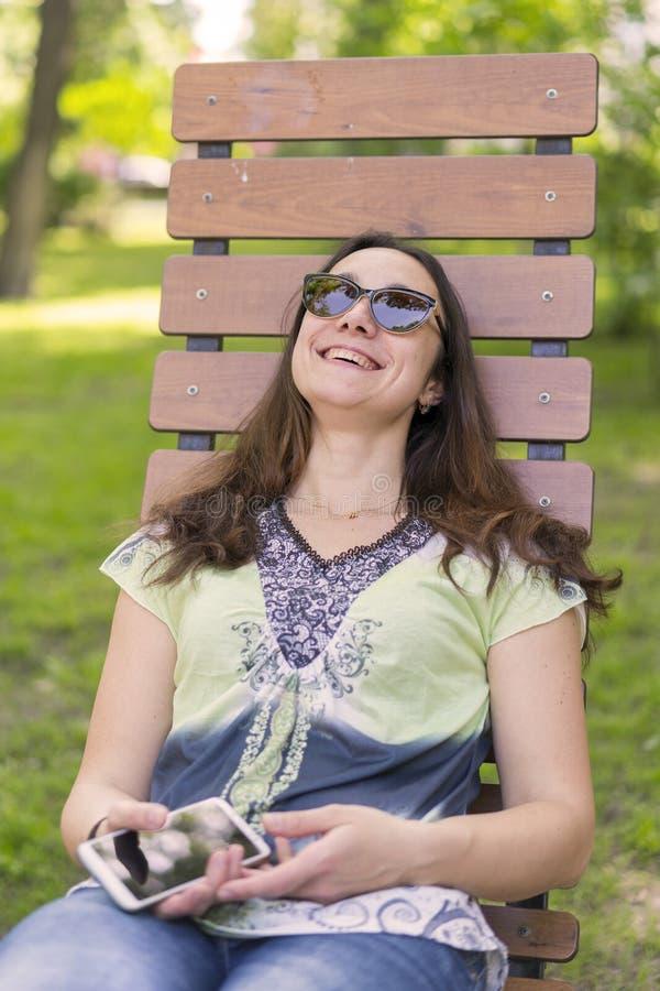 Mujer joven que descansa en el parque en el banco Relajación femenina hermosa en un banco de parque foto de archivo libre de regalías