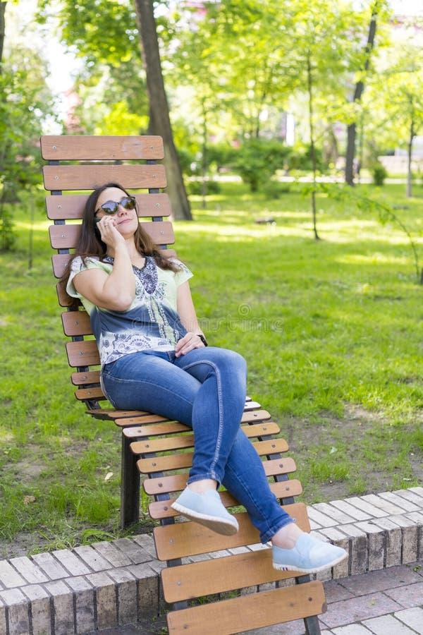 Mujer joven que descansa en el parque en el banco Relajaci?n femenina hermosa en un banco de parque y usar un smartphone entonado fotografía de archivo