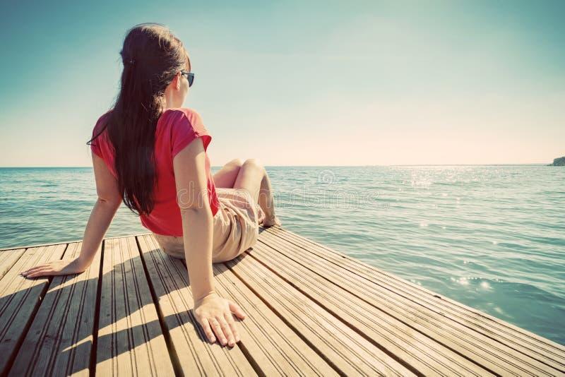 Mujer joven que descansa sobre el embarcadero que mira el mar tranquilo en día de verano soleado foto de archivo libre de regalías